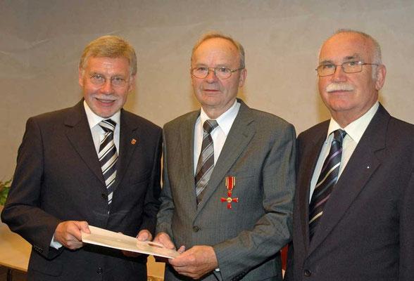 Landrat Konrad Püning überreichte Albert Kortenbusch das Bundesverdienstkreuz. Rechts der stellvertretende Bürgermeister Karl-Heinz Lueg.
