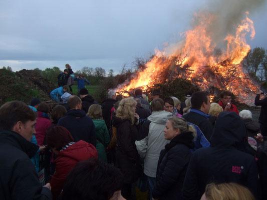 Trotz des unbeständigen Wetters brennt das Osterfeuer sofort und wird von dem Wind stark angefacht