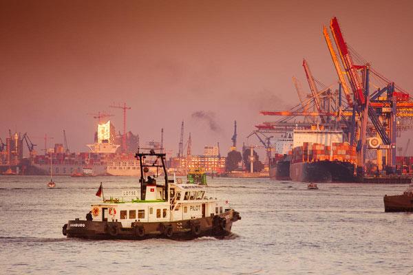 Lotsenboot auf der Elbe im Hamburger Containerhafen und Elbphilharmonie zur goldenen Stunde