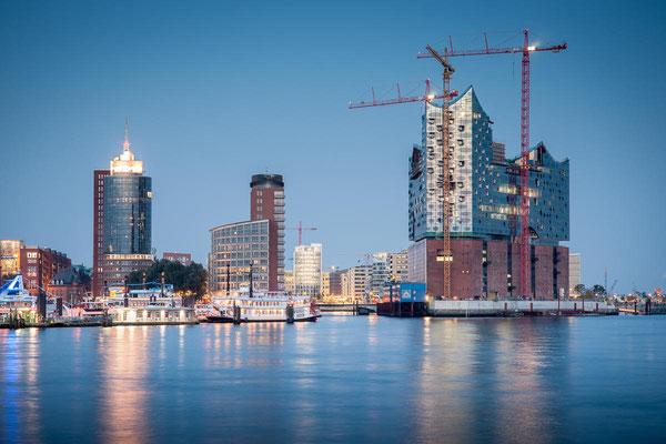 Blick über die Elbe auf Hamburgs Elbphilharmonie im Bau zur blauen Stunde