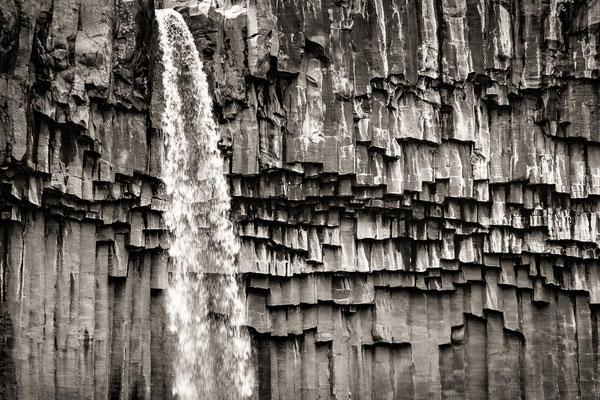 Island: Ein Wasserfall stürzt über eine Wand aus Basaltsäulen