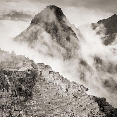 Peru: Die Terrassen von Machu Picchu. Nebel zieht aus dem Tal hoch.