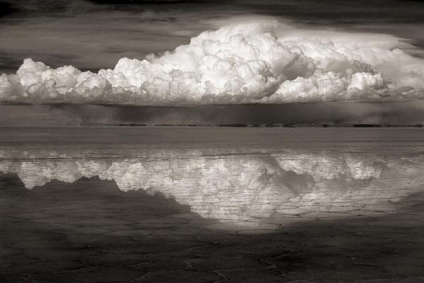 Bolivien zur Regenzeit: Im Wasser des Salar De Uyuni spiegelt sich eine aufbauende Gewitterwolke.