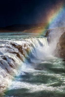 Island: Ein Regenbogen über dem Gullfoss Wasserfall. Am Horizont naht ein Sturm.
