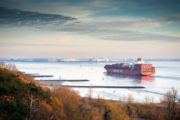Blick über die Elbe mit Containerschiff und das Airbuswerk am Horizont