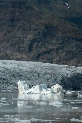 Island: ein kleiner Eisberg treibt in der Lagune des Jökulsárlón Gletscher. Im Hintergrund ein steiler Berghang.