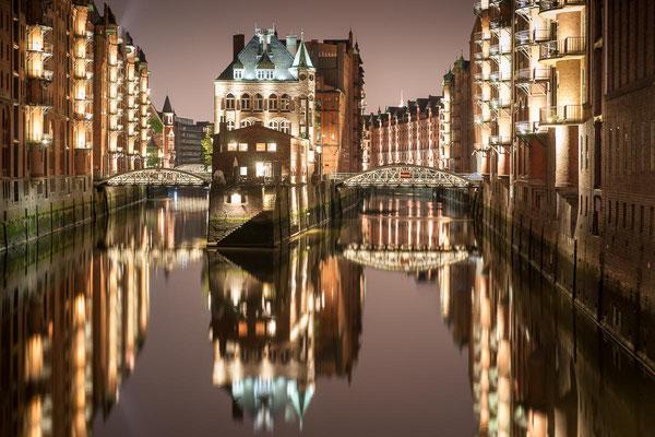 Hamburgs beleuchtete Speicherstadt spiegelt sich nachts im ruhigen Wasser des Fleets