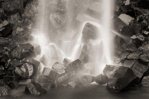 Island: Ein Wasserfall verhüllt Felsenbrocken aus Basaltsäulen