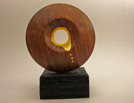 "Skulptur ""Sonnenauge"" - Amazonas-Palisander, geölt, vergoldet (24 Karat); DM 22,5 x 4 cm, Sockel: Mooreiche; 13 x 11 x 6 / Preis: 650,00 €"