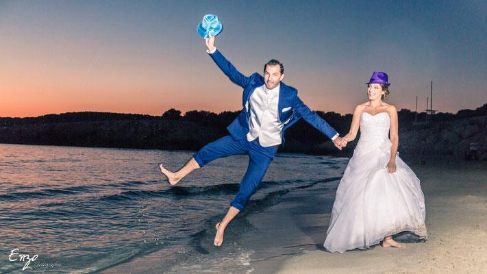 Jeune couple de marié heureux qui sautent de joie à la plage de Sainte croix