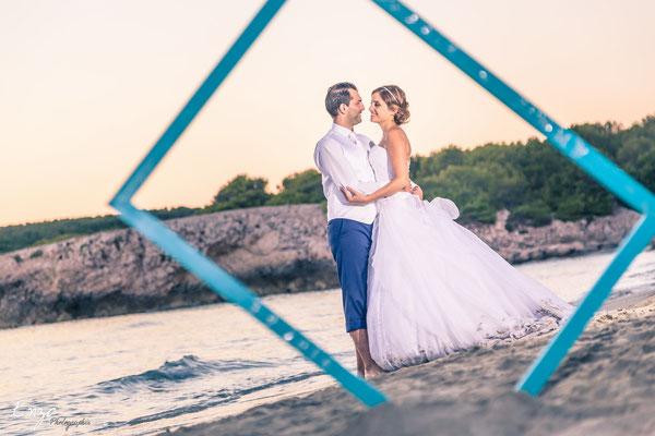 Jeunes mariés en bord de mer entourée par un cadre photo
