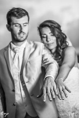 Photo en noir et blanc de jeunes mariées avec un gros plan sur les alliances