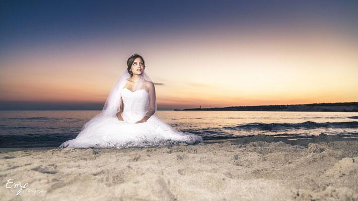 Photo d'une jeune mariée assise sur le sable de la plage de sainte croix