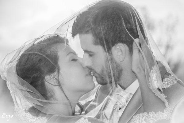 Jeunes mariés qui s'embrassent sous un voile, photo noir et blanc