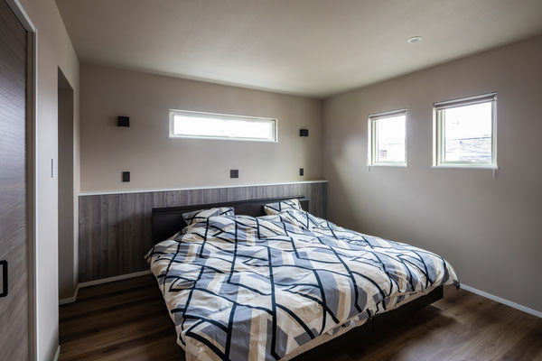 寝室はベージュ調のアクセントクロスで落ち着いた空間に。造作したヘッドボードは小物を置いたりとマルチに活用できます。