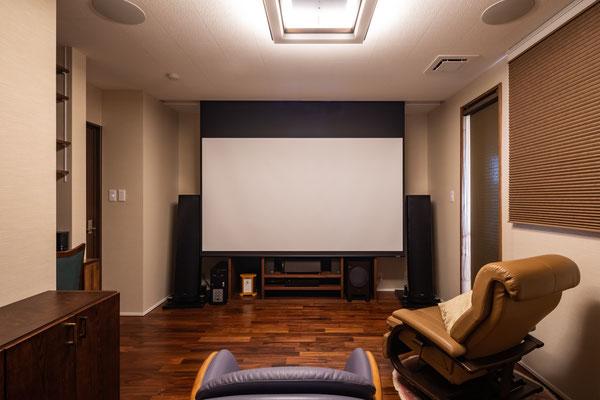 格納式大型スクリーンを備えたシアタールーム。スピーカーはお父様から譲り受けた物。ご実家でお父様が愛用していた棚もピッタリと収まるように設計しました。