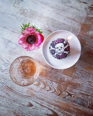 St. Pauli- cupcake mit Totenkopf bemalt. Daneben ein Glas und eine pinke Blume