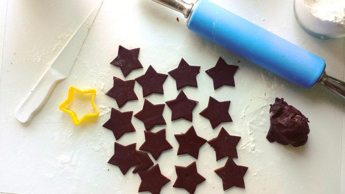 dunkle Mürbteigkekse in Sternform ausgestochen und Rollholz