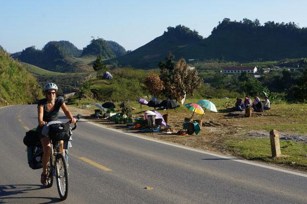 Sur les bords de route, on retrouve souvent des femmes vendant leur production locale à l'ombre de leur parapluie