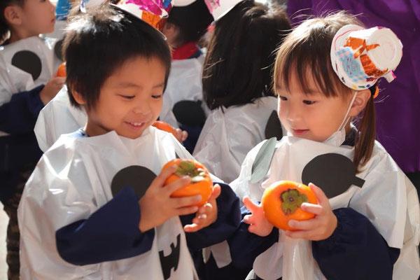 ハロウィン柿を手に取り喜ぶ子どもたち