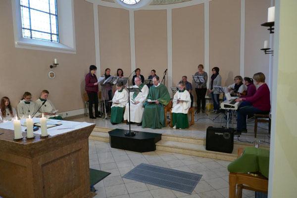Zahlreiche Messdiener, der Kreis für junge Musik und Diakon Thomas Becker zusammen mit Pfarrer Holger Schmitz während der Messe