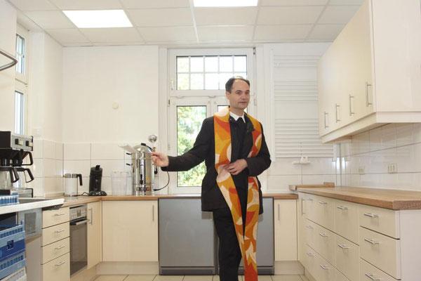 Pfarrer Holger Schmitz segnet die von Grund auf renovierte Küche im Gemeindeheim
