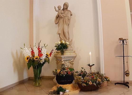 Vor der Marien-Statue aufgestellte Kräuter