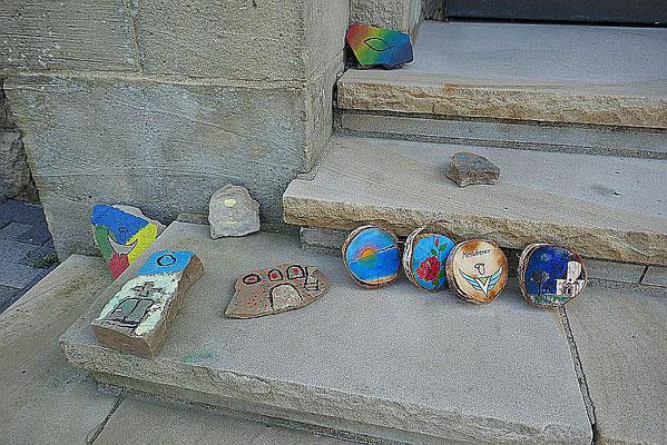 Bemalte Steine und Baumscheiben auf der Kirchentreppe