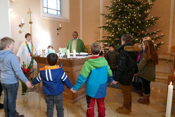 """Kommunionkinder beim """"Vater unser"""" um den Altar"""