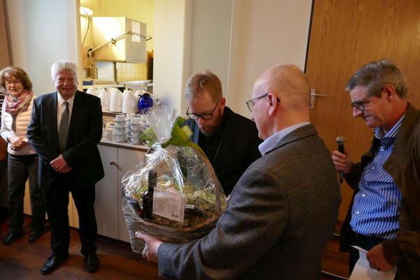 Andreas Damsky übergibt für den Kirchenvorstand einen Korb mit Leckereien