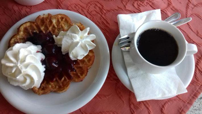 Eine gute Tasse Kaffee und eine Waffel mit Kirschen und Sahne