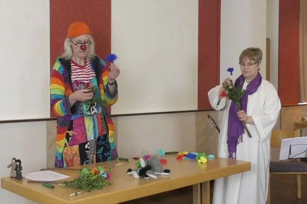 Doro Lohmann und Angela Hoppe basteln Palmstöcke während des Gottesdienstes