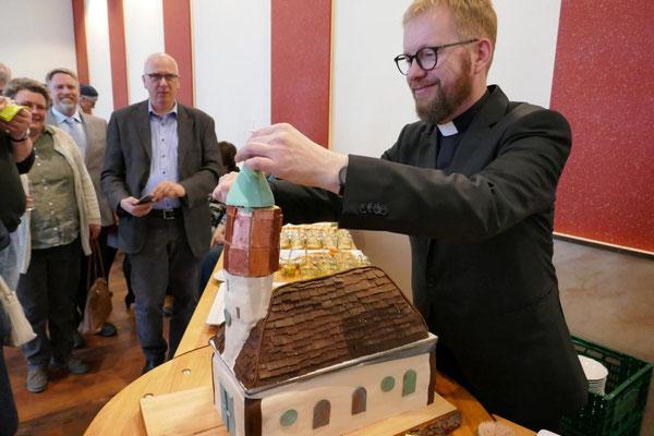 Pfarrer Schmelz schneidet die von Messdienern gebackene Kirche St. Josef an