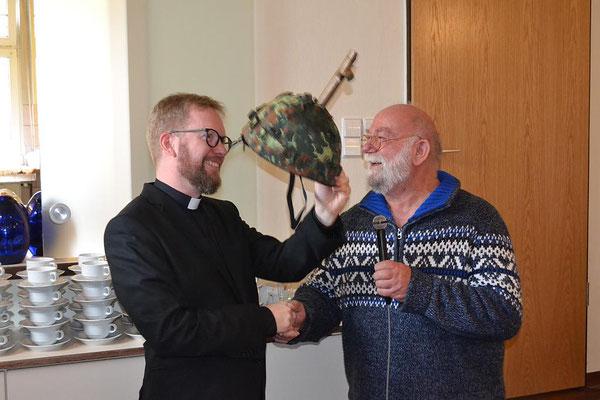 ... und übergibt dem zukünftigen Militärgeistlichen einen Helm mit Kreuz