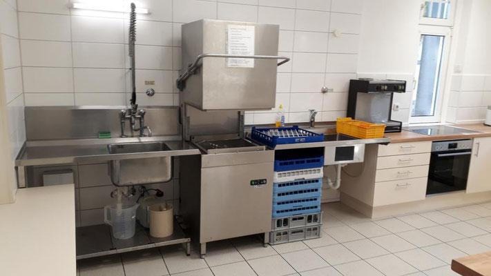 Blick auf Spülmaschine und zwei Spülbecken, die Kaffeemaschine und den Herd mit großem Kochfeld