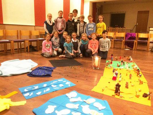 Erstkommunionkinder hinter ihren erarbeiteten Bodenbildern