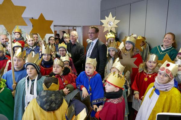 Bürgermeister Ulli Winkelmann und Beigeordneter Volker Hoven inmitten der Sternsinger