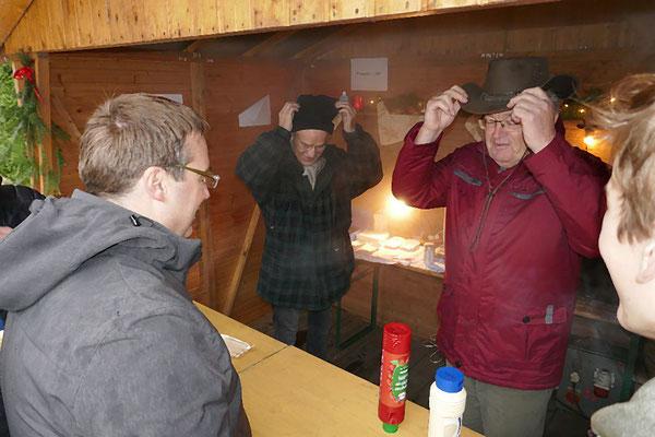 """Die Männer in der """"Pommesbude"""" richten ihre Kopfbedeckungen"""