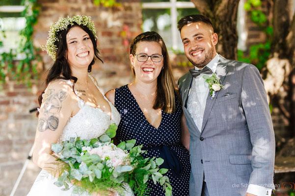 Brautpaarfoto Braut mit Brautstrauß und Bräutigam mit Traurednerin