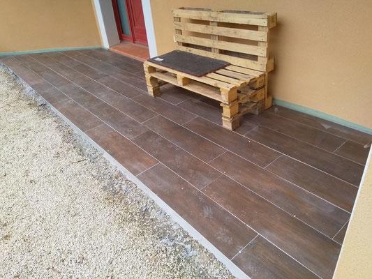 Un petit banc pour la détente sur une jolie terrasse imitation lame de parquet