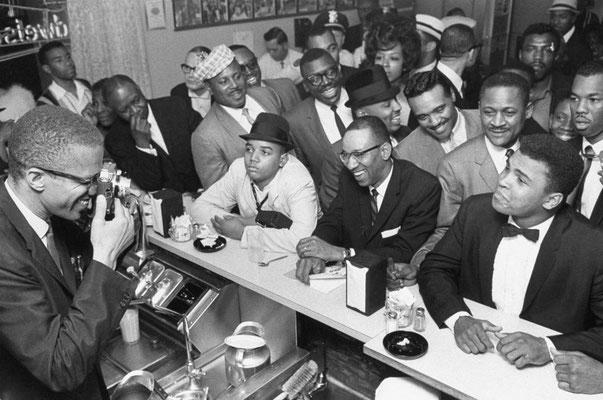 Malcolm X fotografa Muhammad Ali seduto in una diner e circondato da suoi tifosi, dopo la vittoria per il titolo dei pesi massimi su Sonny Liston, sconfitto a Miami nel 1964 (Bob Gomel, TIME & LIFE Pictures/Getty Ima