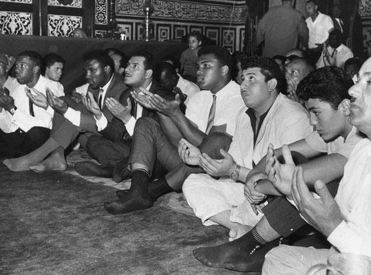 Muhammad Ali (quarto da destra) prega con le mani aperte in una folla alla moschea Hussein al Cairo, 1964, Egitto (GettyImages/Express)