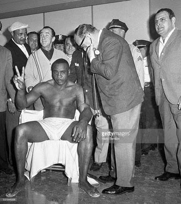 Sonny Liston alza due dita, prevedendo una sconfitta per knockout del suo sfidante Cassius Clay al secondo round, alla visita medica prima del combattimento, Miami, USA, 25 Febbraio 1964 (Harry Benson/Contour by Getty Images)