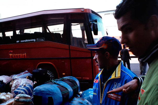 Boarding the luggages in the bus. On the right, Mohammed, seventeen years old, a construction worker. He speaks perfectly as a native the complex Naples dialect more than italian.