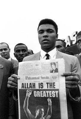 """Muhammad Ali mostra il giornale """"Muhammad Speaks"""" con in prima pagina una sua foto, dopo la cerimonia del peso al Las Vegas Conventional Center x difendere il titolo da Floyd Patterson, suo sfidante il 22 Novembre 1965 (AP Photo/Sal Veder)"""