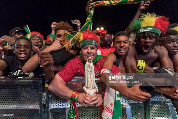 Tifosi portoghesi, uno con una statuetta della Vergine di Fatima tra le mani, festeggiano la vittoria della loro nazionale alla finale con la Francia dell'UEFA Euro 2016 proiettata su schermo gigante in Praca do Comercio, Lisbona, 10 Luglio 2016