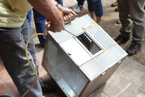 Cage à paquets d'abeilles sans la trémie. Fernand nous montre qu'il faut mouiller les abeilles. Il utilise un pulvérisateur avec de l'eau.