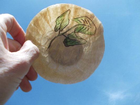 naturbraune Schale mit Blattmotiv gegen das Licht gehalten