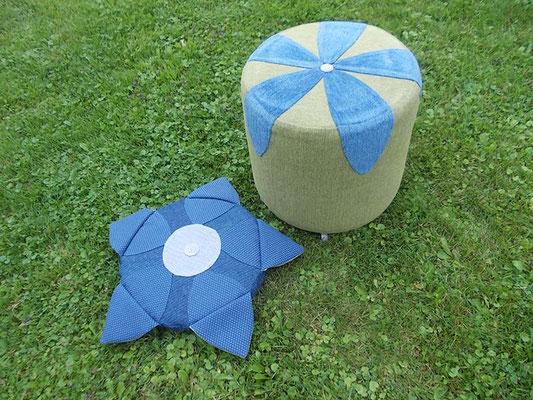 grün-blauer Blumenhocker neben farblich passendem Polster