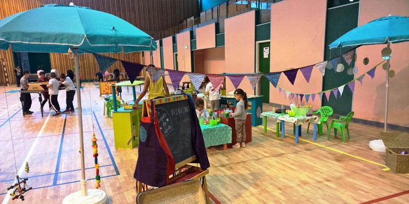 espace de jeu symbolique et d'éveil sur le thème de la guinguette : restaurant, étals de marchand, stands et jeux d'adresse en bois